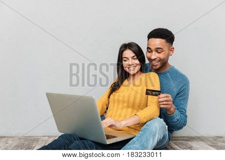 Smiling couple sitting on floor and using laptop and credit card for buying isolated