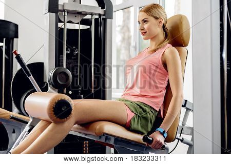 Side view woman demonstrating gladness. She making leg extensions on sport equipment
