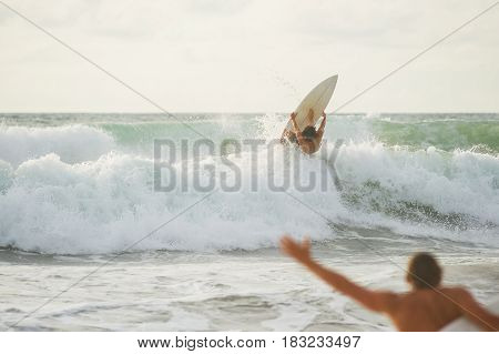 Surfer with a tanned body performs a trick on a short board - a jump over the waves. Extreme water sports, fun at the oceanfront surfing. The surfer rolls on the waves at sunset.