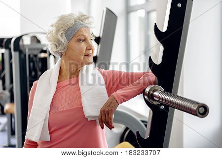 Sports are always in fashion . Cheerful granny looking at mirror in fitness center. She reclining against barbell while looking at window