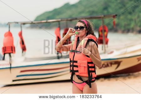 A young girl in a life jacket on the ocean coast stands on the background of a rescue boat. A beautiful curly girl with a bright manicure in an orange life jacket monitors the safety on the beach.