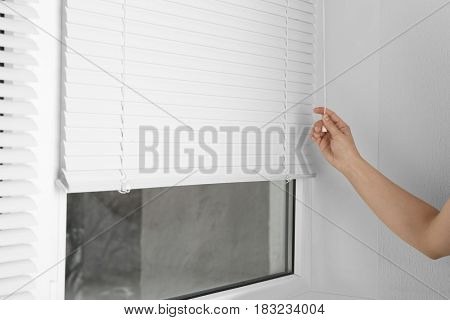 Female hand opening white jalousie on window