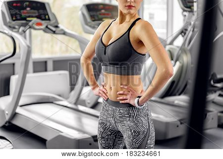 Serene young woman training in modern fitness center. She locating near cross trainers. Focus on her slim figure