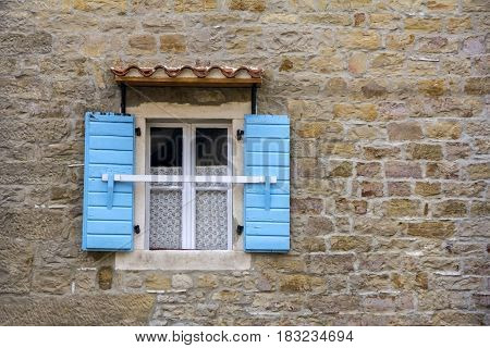 Blue wooden window shutters on the old stone house