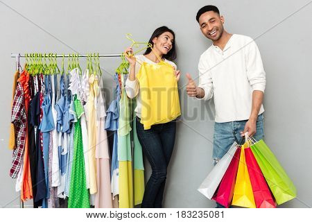 Photo of young happy loving couple standing over grey wall while holding shopping bags and showing thumbs up.