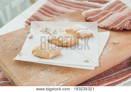 Fresh Pastry With Various Fillings Sprinkled With Powdered Sugar On The Wooden Board. Selective Focu