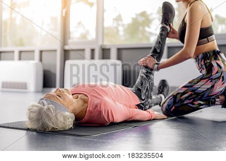 Old woman demonstrating composure while doing stretching in fitness center