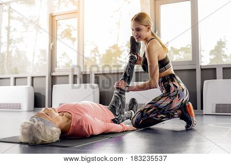 Outgoing female training calm retiree in fitness center. She lying on floor