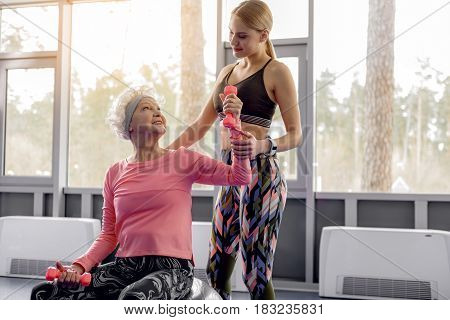 Outgoing beneficiary speaking with cheerful young trainer during exercise in fitness center