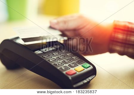 Man tapping a contact less credit card
