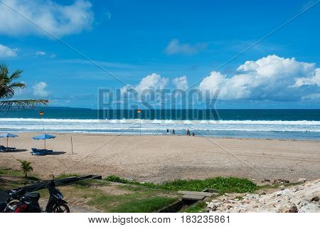 Clean empty tropical beach with sunbeds under the umbrella and a beautiful view of the calm ocean under the blue sky. Travel and leisure on the island, beach vacation. Morning on the beach.