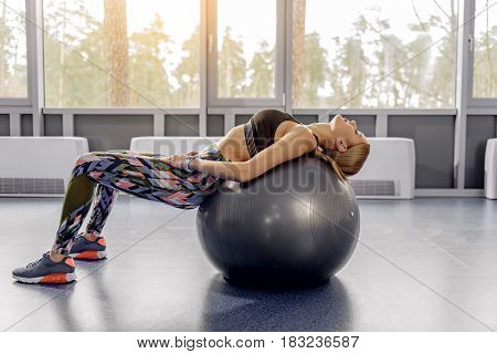 Full length calm female leaning on fitball in gym. She doing exercises with it