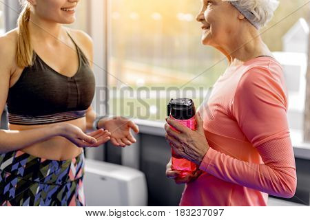 Smiling retiree speaking with cheerful female in health club. She keeping blender bottle in hand