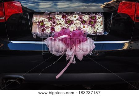 Closeup view on flower decoration on modern wedding car.