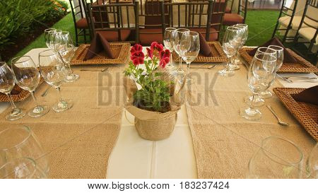Floral arrangement in a pot with rustic cloth wrap on a table arranged and decorated for a lunch in the garden of a house in the morning