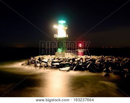 Green lighthouse in Warnemunde shinning at the end of stony pier in the dark night