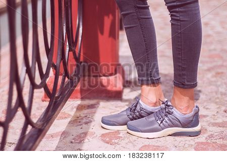 Young girls foot in jeans and sneakers sports shoes walking on road near metal fence. Leisure and lifestyle