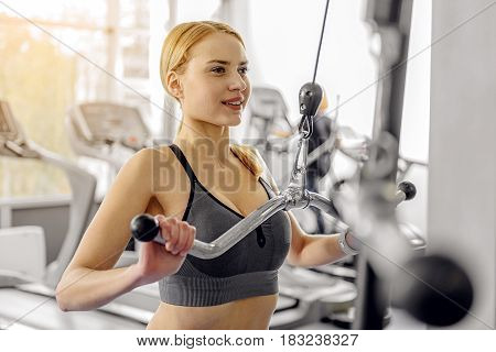 Smiling woman working out with pulldown station in gym. She pumping hands