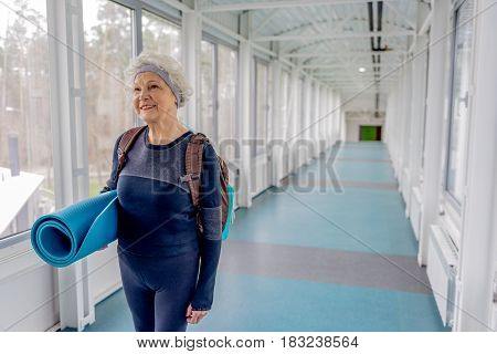 Old woman demonstrating gladness while walking along corridor after pilates exercises in fitness center. Portrait