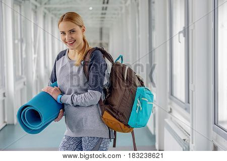 Outgoing young female standing in long hall after after good training in modern gym. Portrait