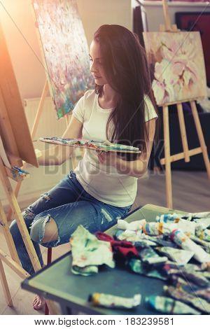 Female Artist Working On Painting In Studio.