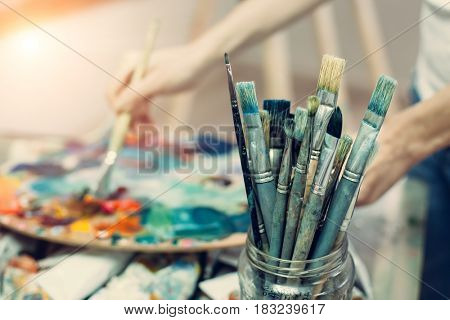 Palette, brushes, paints, selective focus on the foreground. Background image.