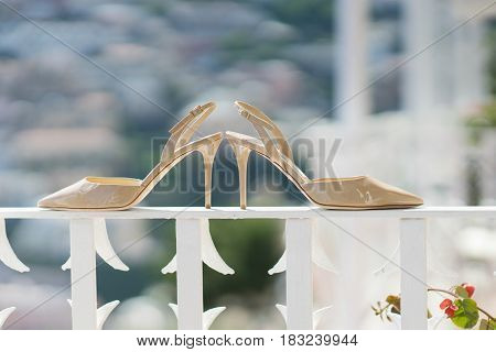 Bridal beige shoes on a white railing - wedding accessory