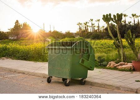City trash cans. Green overfilled trash dumpster