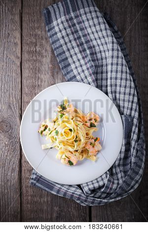 Tagliatelle with shrimps on a wooden surface