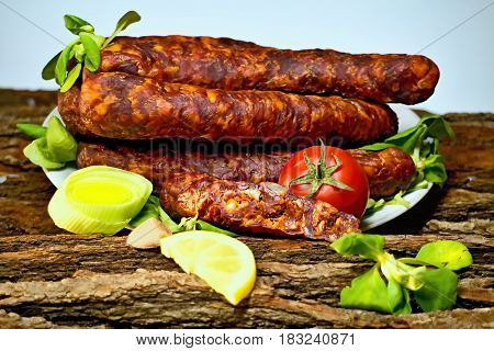Tasty smoked sausages with fields salad ready for consumption.