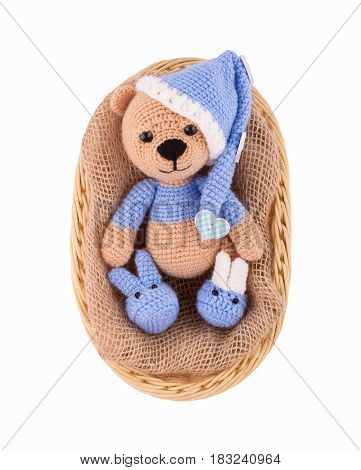 A small knitted teddy bear in a wicker basket. A sleepy bear cub in a hat and booties. Amigurumi. Handmade. Isolated on white.