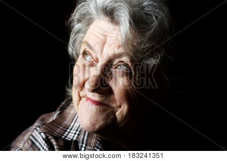 Elderly woman smile and thoughtful face on a black background