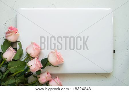 Notebook and flower bouquet at white stone table. Top view copy space. Work and holiday concept.