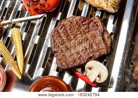 Horizontal close-up shot of meat cooked on electric grill from above.