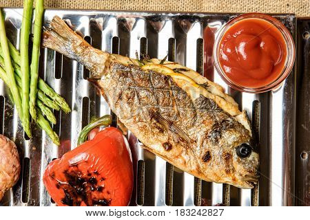 From above cooked on electric grill fish with sauce. Horizontal studio shot.