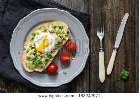 Healthy breakfast toast: poached egg, mashed avocado with cilantro and lime juice, sunflower seeds and cherry tomatoes on a plate on wooden table background. Top view