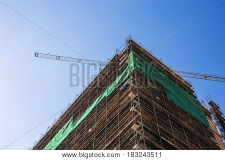 Building crane and building under construction against blue sky.