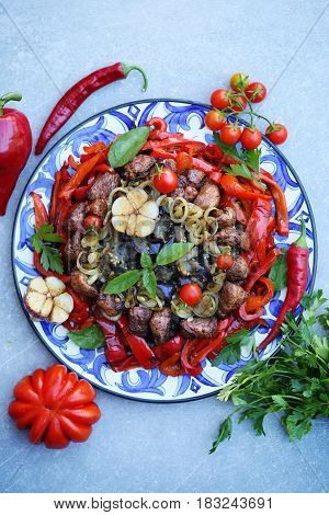 Fried meat with fried eggplants, peppers and onions