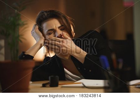 Young woman designer yawning in office at workplace
