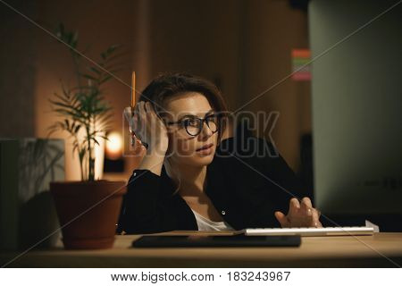 Image of serious young lady designer sitting indoors at night using computer. Looking aside.