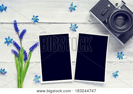 vintage retro camera, blank photo frames and spring blue flowers bouquet on white wooden background. mock up. top view. vintage toning