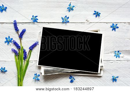 blank photo frame and spring blue flowers bouquet on white wooden background. mock up. top view. sprig concept