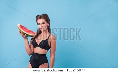Picture of young woman holding a big slice watermelon in the studio. Copyspace
