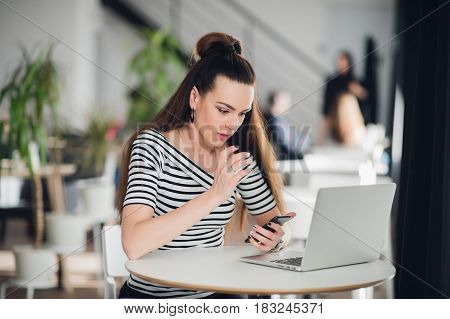 Photo of shocked young woman with long hair sitting at the table in cafe and looking at her phone with mixed expression