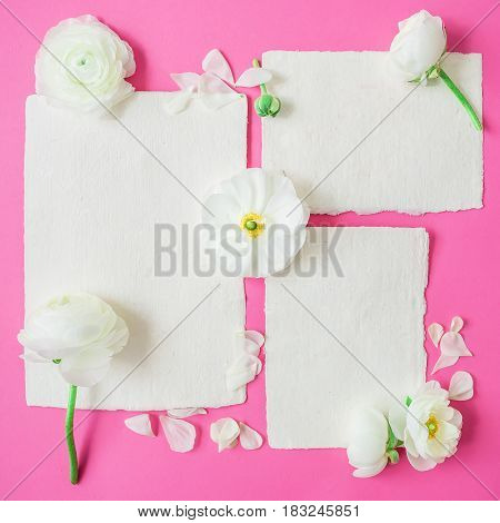 Paper calligraphy cards and envelope with white flowers on pink background. Flat lay, top view. Flowers background.