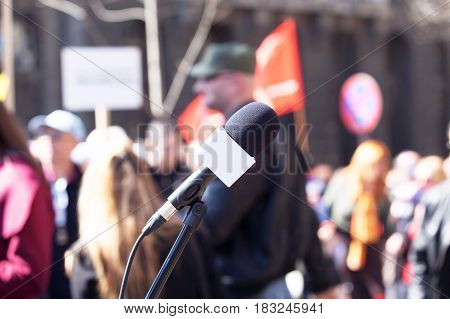 Political protest. Demonstration. Microphone in focus, blurred protesters in background.