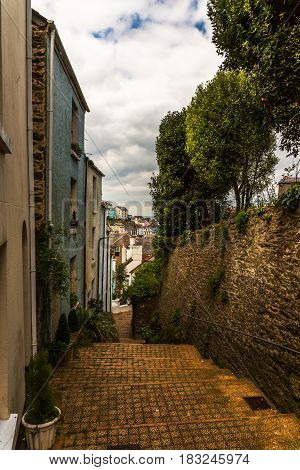 Colorful buildings along the stairs next to the stone wall descent down green vegetation seaside climate