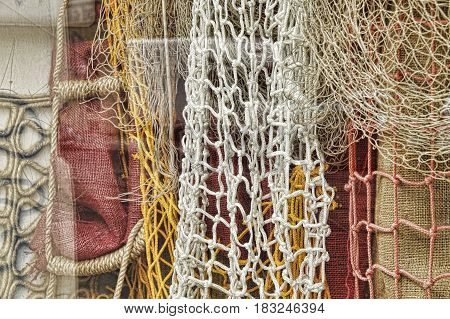 Fishing net's on display in a shop window yellow and white net's hanging with red and brown canvas as backdrop.