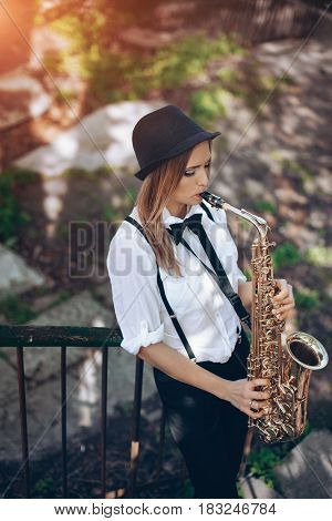 Beautiful Young Girl Plays A Saxophone Standing On Steps - Outdoors. Attractive Woman In White Shirt