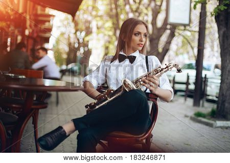 Young Attractive Girl In White Shirt With A Saxophone Sitting Near Caffe Shop - Outdoor In Sity. Sex